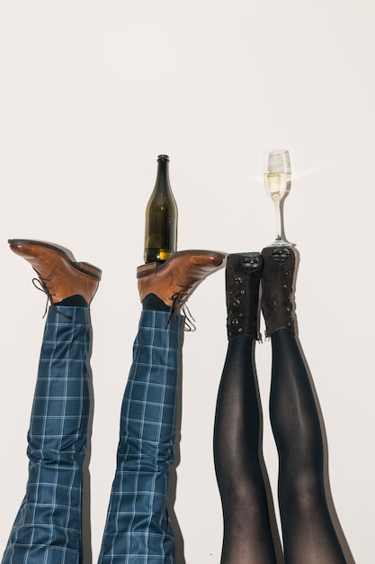 Champagne bottle and glass on feet Free Photo