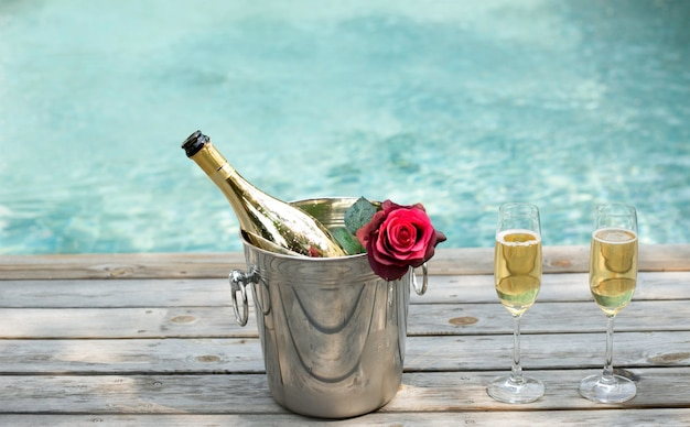 Champagne bottle in ice bucket and champagne glass by swimming pool Premium Photo