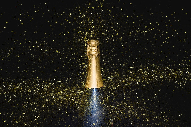 Champagne bottle with falling sequins Free Photo