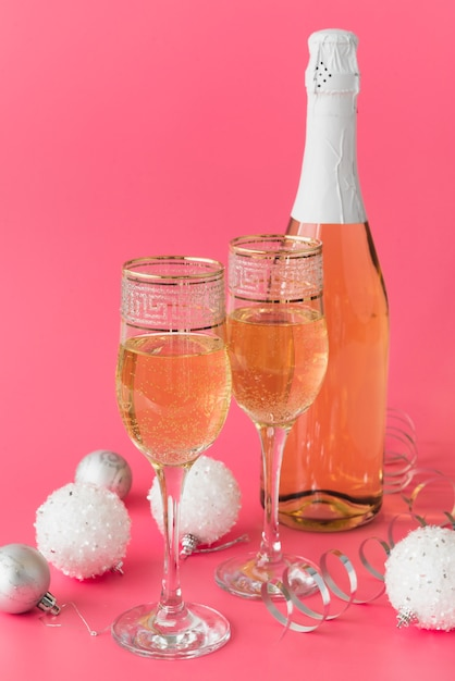 Champagne bottle with glasses and christmas balls Free Photo