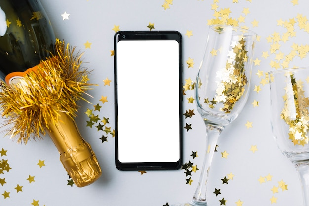 Champagne bottle with smartphone on table Free Photo