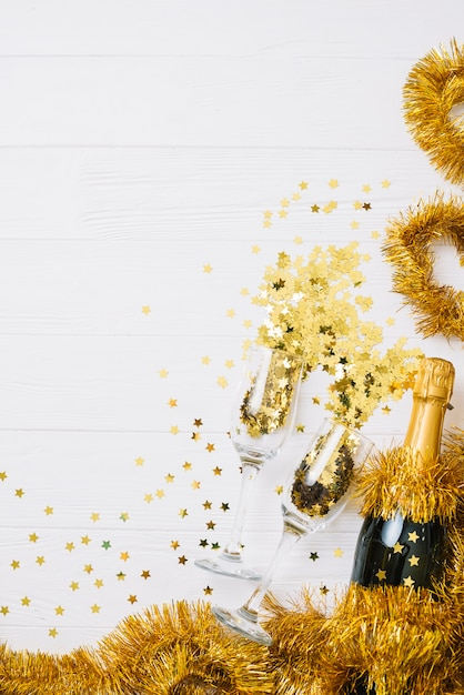 Champagne bottle with tinsel on table Free Photo