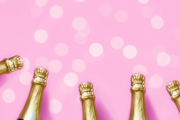 Champagne bottles on a pastel pink background with bokeh lights Premium Photo