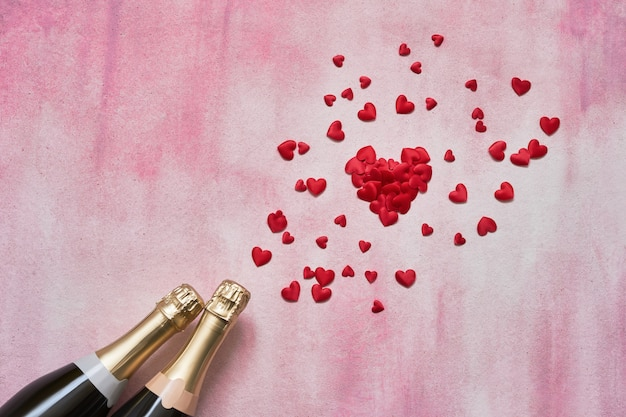 Champagne bottles and red hearts on pink background. Premium Photo