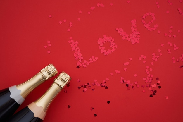 Champagne bottles with confetti forming word love on red background. Premium Photo