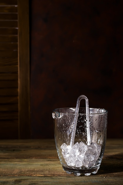 Champagne bucket full with ice on dark wooden background, shadows and copy space Premium Photo