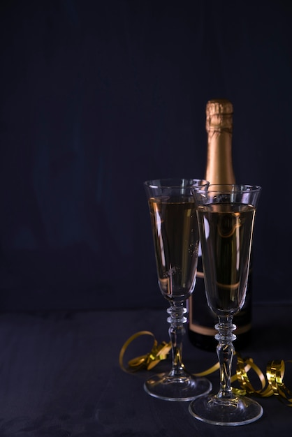 Champagne glass and bottle with streamers on black background Free Photo