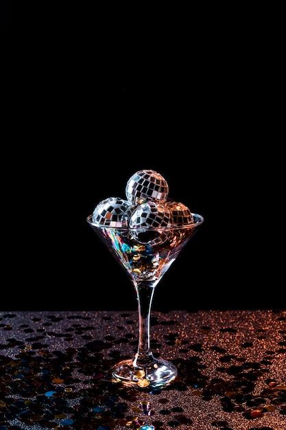 Bicchiere di champagne riempito con palline da discoteca Foto Gratuite