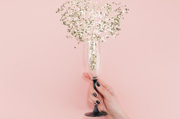 Champagne glass poured out golden stars confetti Premium Photo