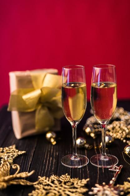 ギフトボックスとクリスマスの装飾が施されたシャンパングラス。特別なものにプレゼント。 無料写真
