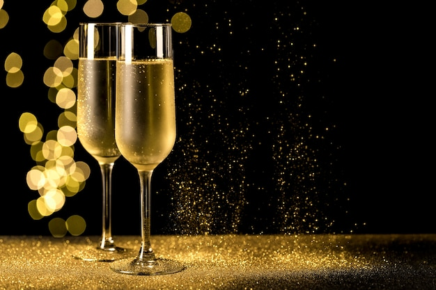Champagne glasses with bokeh lights Free Photo