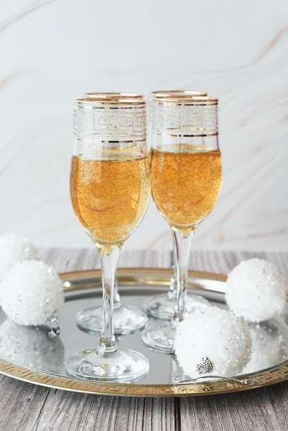 Champagne glasses with christmas balls on a tray Free Photo