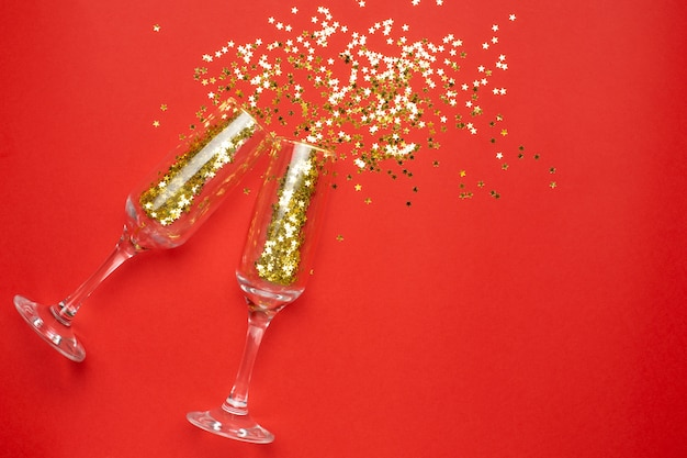 Champagne glasses with golden stars confetti, christmas and new year concept Premium Photo