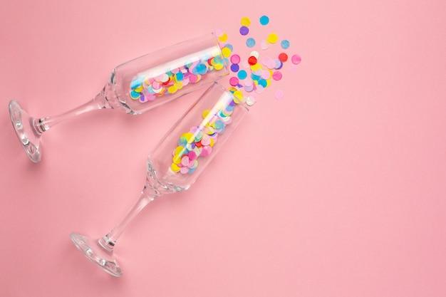 Champagne glasses with multi-colored confetti on pink Premium Photo