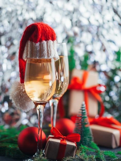 Бокалы с шампанским и шляпы санты Premium Фотографии