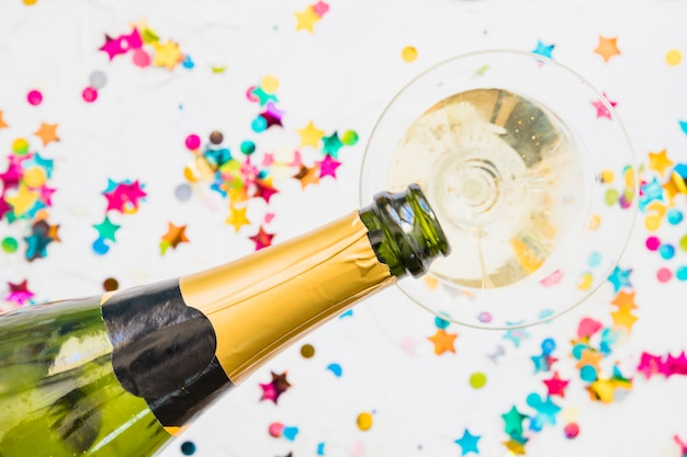Champagne pouring in glass from bottle on table Free Photo