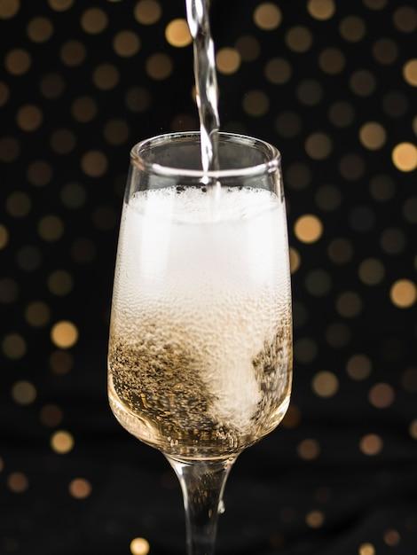 Шампанское наливая в бокал с пеной Бесплатные Фотографии