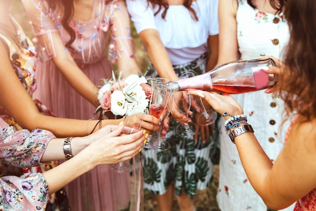 Champagne with glasses in girls hands at hen party outdoor. Premium Photo