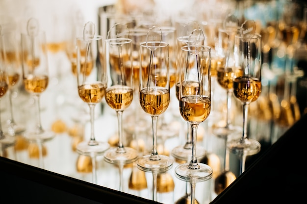 Champaigne si riempie di bevande alcoliche sul vassoio con riflesso di mirroir Foto Gratuite