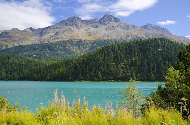 Champfer alpine lake circondato da montagne ricoperte di vegetazione sotto la luce del sole in svizzera Foto Gratuite