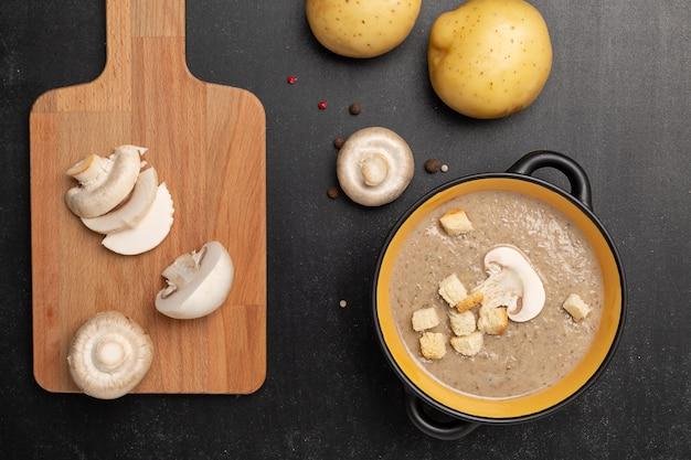Champignon mushroom cream soup in a black bowl Premium Photo