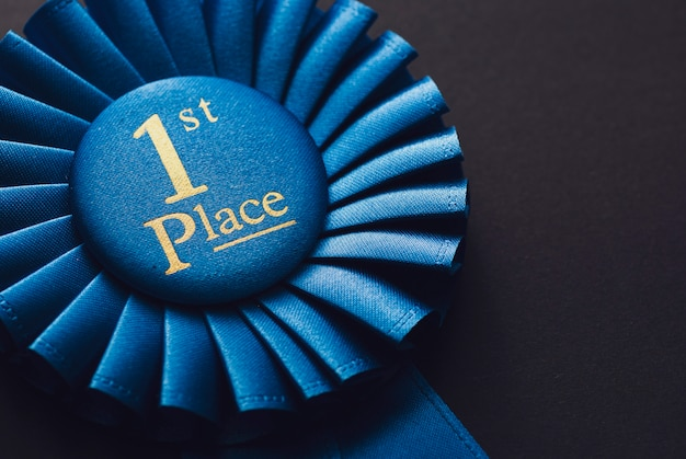 Champion 1st place blue rosette with gold text on black background Premium Photo