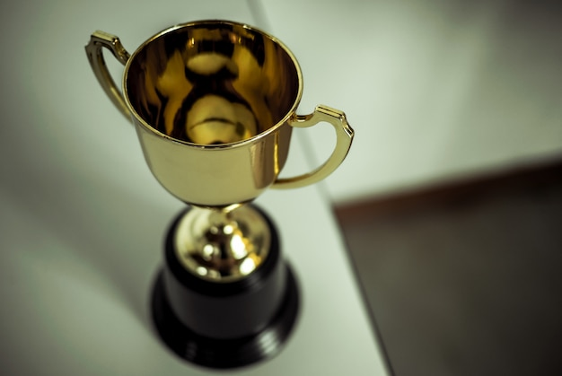 Champion golden trophy placed on table . Premium Photo