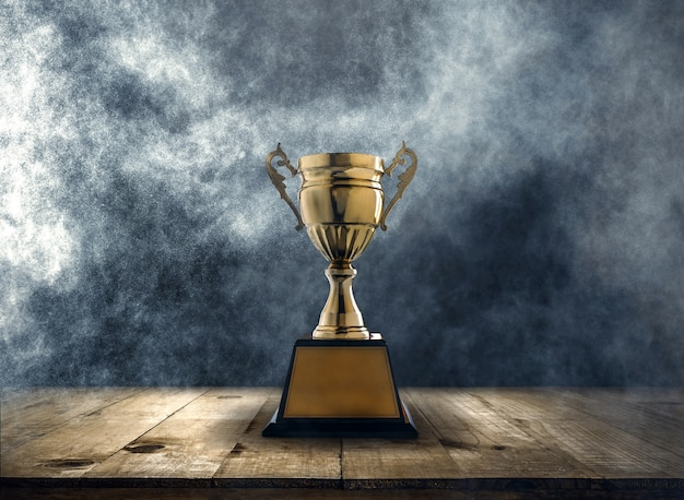 Champion golden trophy placed on a wooden table with dark and smoke background Premium Photo