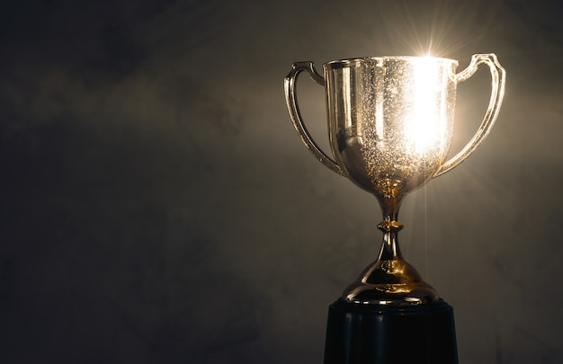 Champion golden trophy placed on wooden table Premium Photo