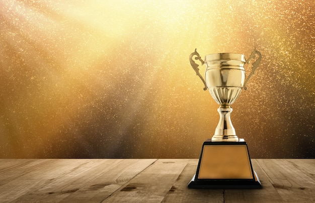 Champion golden trophy on wood table with copy space and gold twinkly lights and glitter Premium Photo