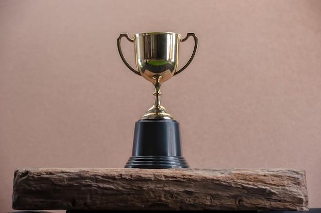 Champion golden trophy on wooden table Premium Photo