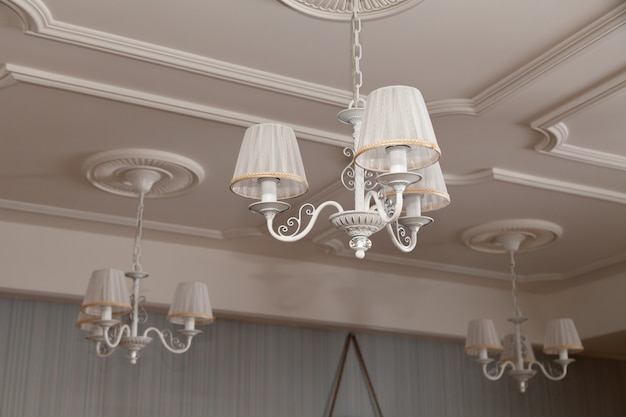 Chandeliers with three electric lamps and lampshades hanging on the ceiling Premium Photo