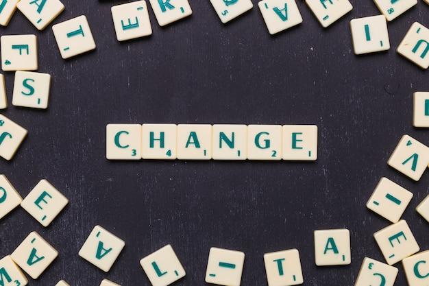 Change scrabble letters arranged over black backdrop Free Photo