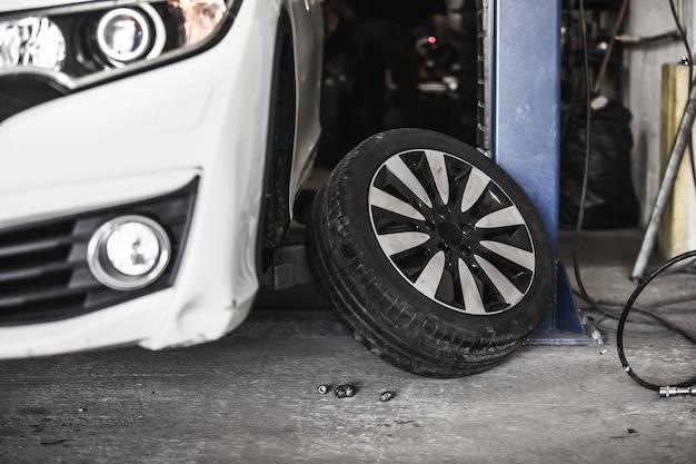 Замена автомобильного колеса на авто, автосервис с поднятым автомобилем, сервисный центр, смена шин Premium Фотографии