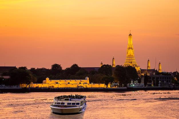 Круизный катер по реке чао прайя с храмом рассвета на закате Premium Фотографии