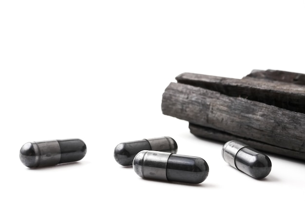 Charcoal (activated carbon) in capsules on white background Premium Photo