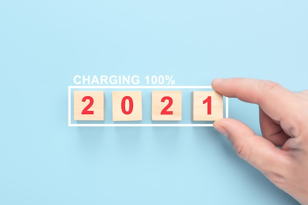 Charging 2021 years on wooden cubes on a blue background. hand putting wood cube in progress bar. Premium Photo