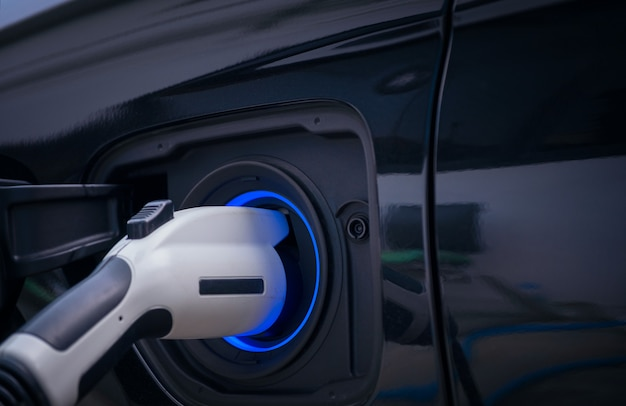 Charging modern electric car battery on the street which are the future of the automobile, close up of power supply plugged into an electric car being charged for hybrid . new era of vehicle fuel. Premium Photo