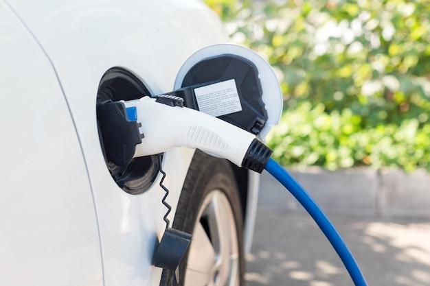 Зарядка современного электромобиля на улице Premium Фотографии