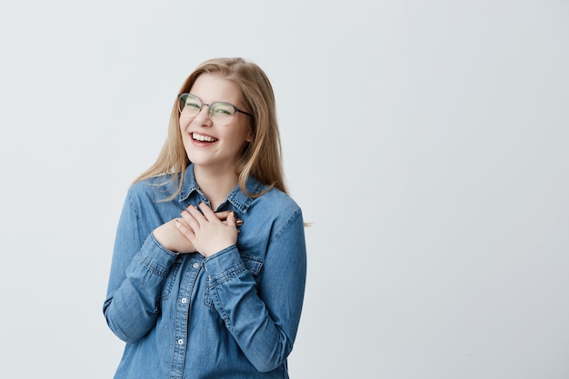 Charismatic and charming young european woman with straight blonde hair wearing stylish spectacles and denim shirt, smiling widely, looking  in expectation of surprise, looking happy Free Photo