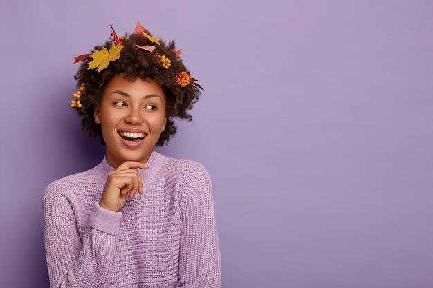 Carismatica bella donna tocca la mascella, distoglie lo sguardo con espressione felice, ha foglie autunnali sui capelli, esprime emozioni positive, vestita in modo casual Foto Gratuite