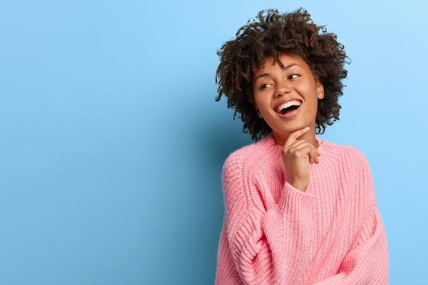 Donna carismatica con un afro che posa in un maglione rosa Foto Gratuite