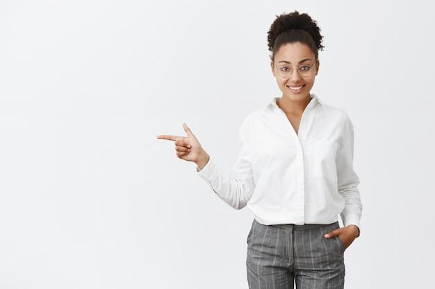 고객에게 방법을 보여주는 매력적이고 친절한 회사원. 안경과 바지에 정중하고 똑똑하고 창의적인 여성 고용주의 초상화, 주머니에 손을 잡고, 왼쪽을 가리키는, 출구에서 표시 무료 사진