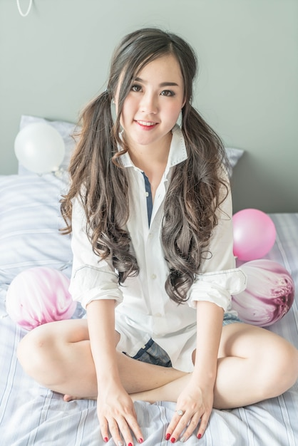 Charming asian woman smiling face lying on the bed Premium Photo