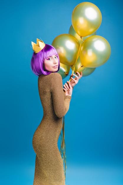 Очаровательная привлекательная модная молодая женщина в роскошном платье с золотыми шарами. стрижка фиолетовая, корона на голове, веселые эмоции, праздник. Бесплатные Фотографии