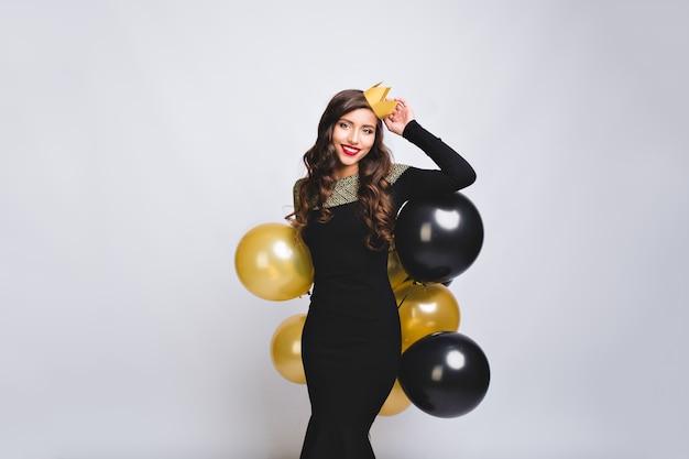 Affascinante donna attraente festeggia il compleanno in abito di lusso nero, con palloncini neri e oro, indossa una corona gialla. divertirsi, festa di capodanno. Foto Gratuite