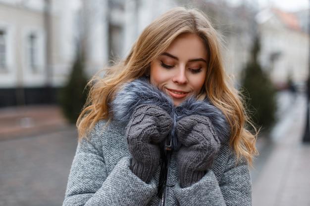 ニットミトンのスタイリッシュな暖かい冬のアウターウェアで金髪の魅力的な魅力的な若い女性は週末を楽しんでいます。かなりファッショナブルな女の子。 Premium写真
