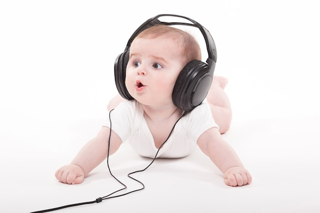 Charming baby on a white  with headphones listening to music Premium Photo