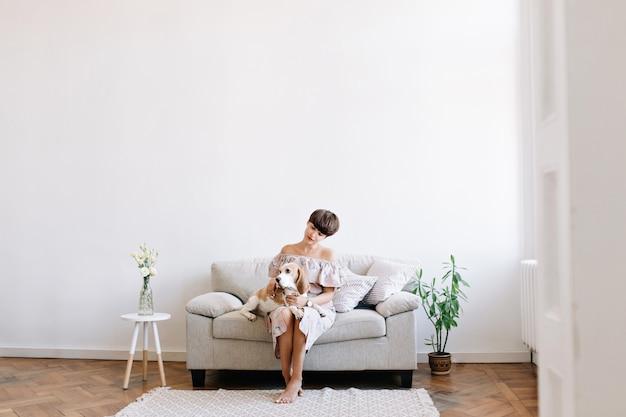 Очаровательная босоногая девушка сидит на сером диване между столиком и зеленым растением, глядя на бигль на коленях Бесплатные Фотографии