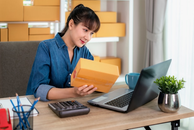 Charming beautiful asian teenager owner business woman work at home for online shopping, checking detail in mailbox with laptop with office equipment, entrepreneur lifestyle concept Premium Photo